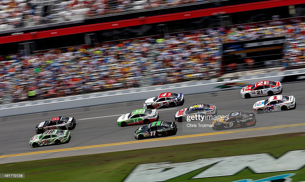 Dale Earnhardt Jr., driver of the #88 National Guard Chevrolet, and Kyle Busch, driver of the #18 Interstate Batteries Toyota, lead a pack of cars during the NASCAR Sprint Cup Series Coke Zero 400 at Daytona International Speedway on July 6, 2014 in Daytona Beach, Florida.
