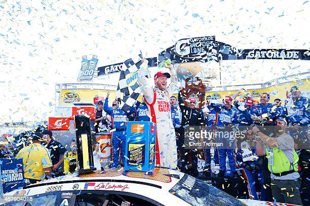 Dale Earnhardt Jr driver of the National Guard Chevrolet celebrates in Victory Lane after winning during the NASCAR Sprint Cup Series Goody's...