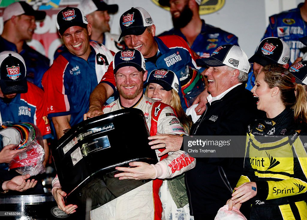 Dale Earnhardt Jr., driver of the #88 National Guard Chevrolet, celebrates in Victory Lane with his girlfriend Amy Reimann, and team owner Rick Hendrick after winning during the NASCAR Sprint Cup Series Daytona 500 at Daytona International Speedway on February 23, 2014 in Daytona Beach, Florida.