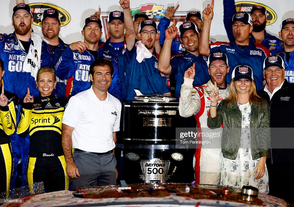 Dale Earnhardt Jr., driver of the #88 National Guard Chevrolet, celebrates in Victory Lane with his girlfriend Amy Reimann, team owner Rick Hendrick and Joie Chitwood III after winning during the NASCAR Sprint Cup Series Daytona 500 at Daytona International Speedway on February 23, 2014 in Daytona Beach, Florida.