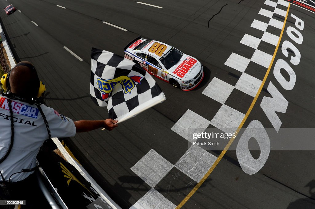 Dale Earnhardt Jr driver of the National Guard Chevrolet crosses the finish line to win the NASCAR Sprint Cup Series Pocono 400 at Pocono Raceway on...