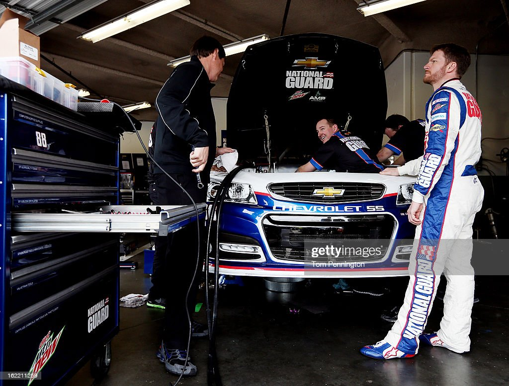 Dale Earnhardt Jr., driver of the #88 National Guard Chevrolet, looks on as crew members work on the car in the garage area during practice for the NASCAR Sprint Cup Series Daytona 500 at Daytona International Speedway on February 20, 2013 in Daytona Beach, Florida.
