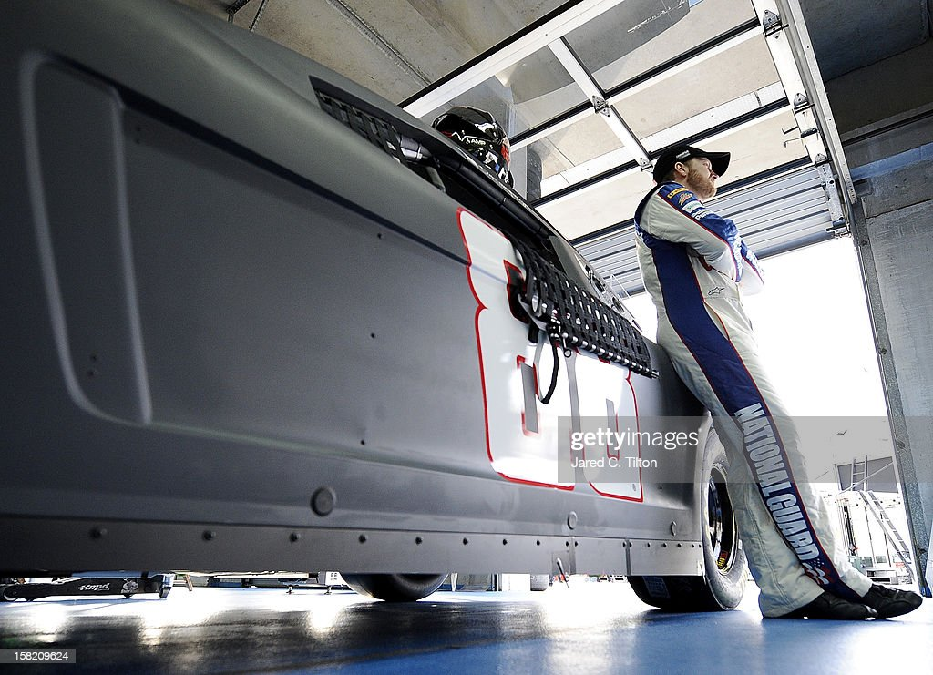 Dale Earnhardt Jr., driver of the #88 National Guard Chevrolet, looks on in the garage area during testing at Charlotte Motor Speedway on December 11, 2012 in Concord, North Carolina.