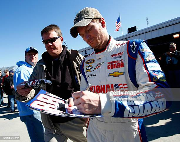 Dale Earnhardt Jr driver of the National Guard Chevrolet signs autographs for fans during practice for the NASCAR Sprint Cup Series Goody's Headache...