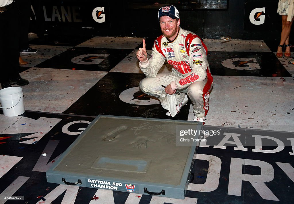 <a gi-track='captionPersonalityLinkClicked' href=/galleries/search?phrase=Dale+Earnhardt+Jr.&family=editorial&specificpeople=171293 ng-click='$event.stopPropagation()'>Dale Earnhardt Jr.</a>, driver of the #88 National Guard Chevrolet, signs his name in cement in Victory Lane after winning the NASCAR Sprint Cup Series Daytona 500 at Daytona International Speedway on February 23, 2014 in Daytona Beach, Florida.