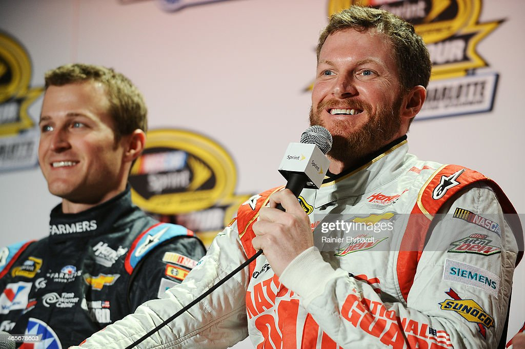 Dale Earnhardt Jr. (R), driver of the #88 National Guard Chevrolet, speaks to the media as Kasey Kahne, driver of the #5 Farmers Insurance Chevrolet, listens during the NASCAR Sprint Media Tour at Charlotte Convention Center on January 28, 2014 in Charlotte, North Carolina.