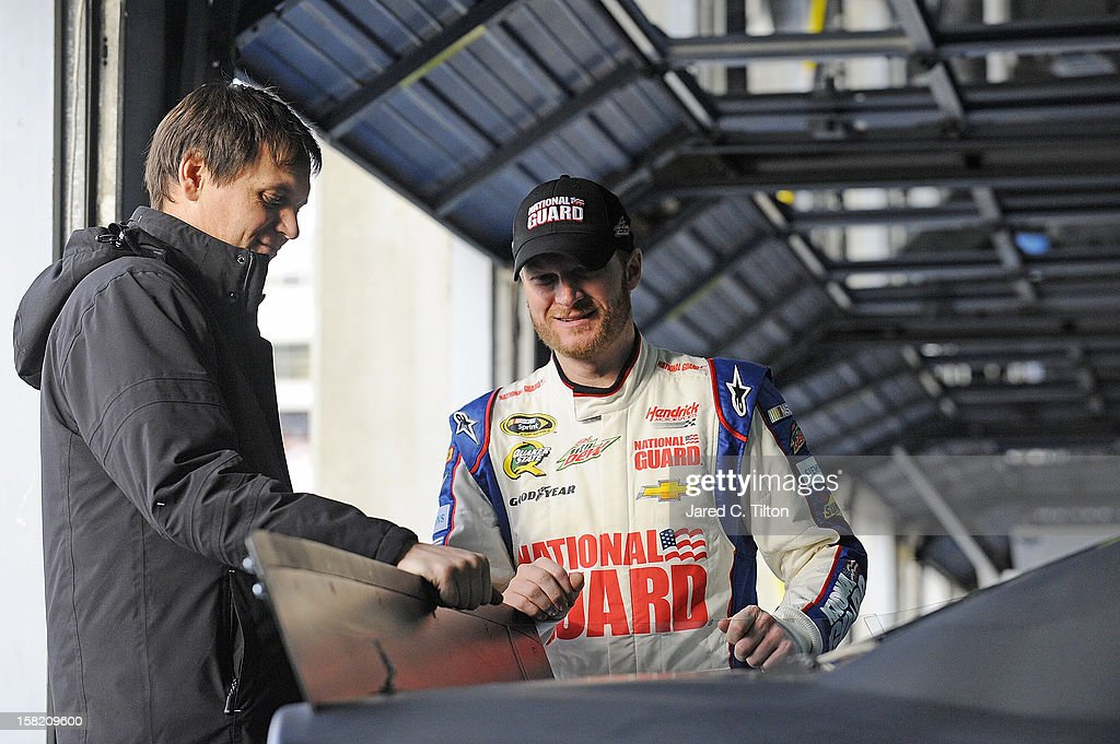 Dale Earnhardt Jr. (R), driver of the #88 National Guard Chevrolet, speaks with crew chief, Steve Letarte in the garage area during testing at Charlotte Motor Speedway on December 11, 2012 in Concord, North Carolina.
