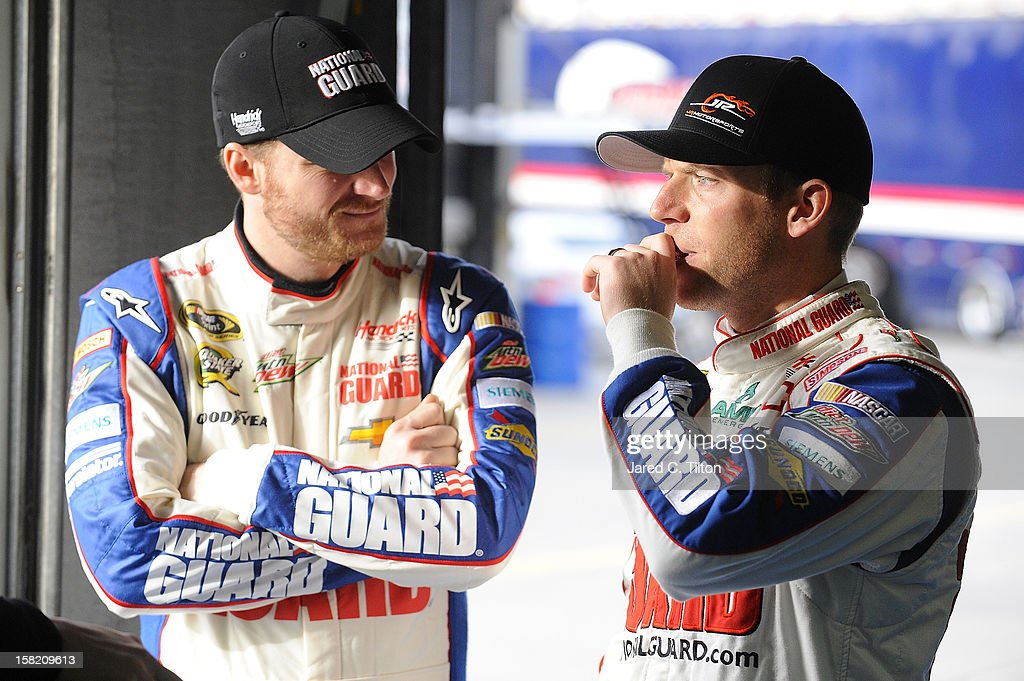 Dale Earnhardt Jr. (L), driver of the #88 National Guard Chevrolet, speaks with Regan Smith, driver of the Hendrick Motorsports Chevrolet, in the garage area during testing at Charlotte Motor Speedway on December 11, 2012 in Concord, North Carolina.