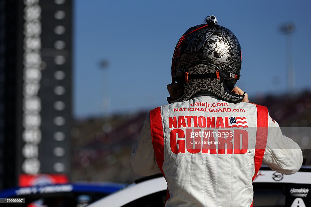 Dale Earnhardt Jr., driver of the #88 National Guard Chevrolet, stands on the grid during qualifying for the NASCAR Sprint Cup Series Auto Club 400 at Auto Club Speedway on March 21, 2014 in Fontana, California.