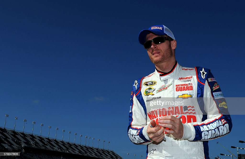 Dale Earnhardt Jr., driver of the #88 National Guard Chevrolet, walks down the grid during qualifying for the NASCAR Sprint Cup Series Coke Zero 400 at Daytona International Speedway on July 5, 2013 in Daytona Beach, Florida.