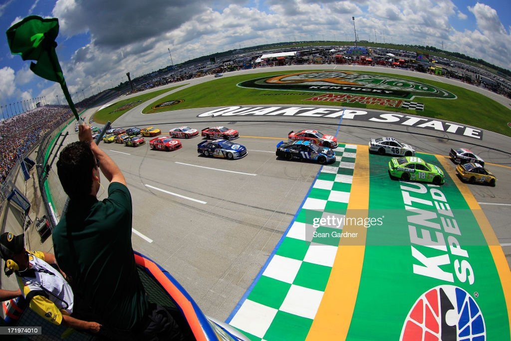Dale Earnhardt Jr., driver of the #88 National Guard Youth Foundation Chevrolet, and Carl Edwards, driver of the #99 UPS Ford, lead the field past the green flag to start the NASCAR Sprint Cup Series Quaker State 400 at Kentucky Speedway on June 30, 2013 in Sparta, Kentucky.