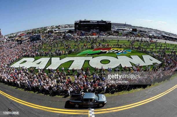 Dale Earnhardt Jr driver of the National Guard/AMP Energy Chevrolet rides past fans in a pickup truck during prerace ceremonies for the NASCAR Sprint...