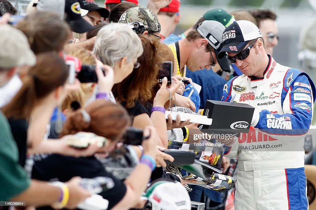 <a gi-track='captionPersonalityLinkClicked' href=/galleries/search?phrase=Dale+Earnhardt+Jr.&family=editorial&specificpeople=171293 ng-click='$event.stopPropagation()'>Dale Earnhardt Jr.</a>, driver of the #88 National Guard/Diet Mtn. Dew Chevrolet, signs autographs during qualifying for the NASCAR Sprint Cup Series Pocono 400 presented by #NASCAR at Pocono Raceway on June 9, 2012 in Long Pond, Pennsylvania.
