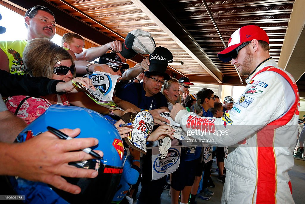 Dale Earnhardt Jr., driver of the #88 National Guard/Superman Chevrolet, signs his autograph for fans in the garage area during practice for the NASCAR Sprint Cup Series Quicken Loans 400 at Michigan International Speedway on June 14, 2014 in Brooklyn, Michigan.