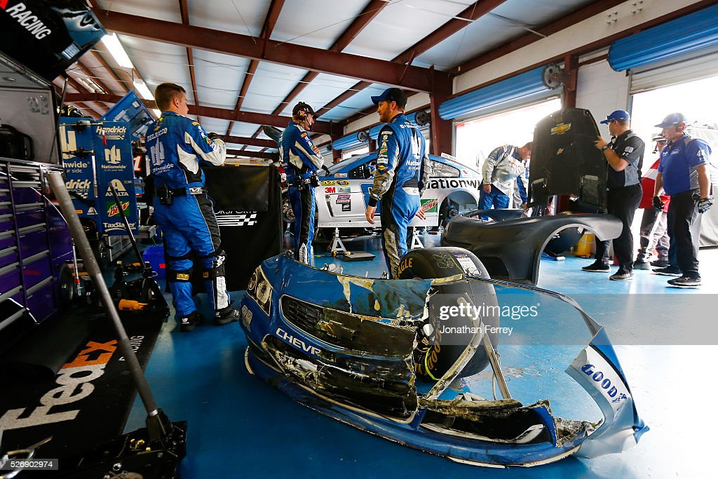 Dale Earnhardt Jr, driver of the #88 Nationwide Chevrolet, looks on as crew members work on his car in the garage area during the NASCAR Sprint Cup Series GEICO 500 at Talladega Superspeedway on May 1, 2016 in Talladega, Alabama.