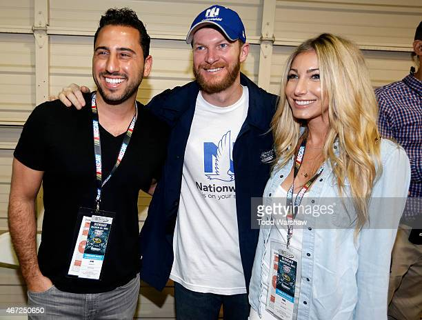 Dale Earnhardt Jr driver of the Nationwide Chevrolet poses for a photo with television personality Josh Altman and his fiance Heather Bilyeu before...