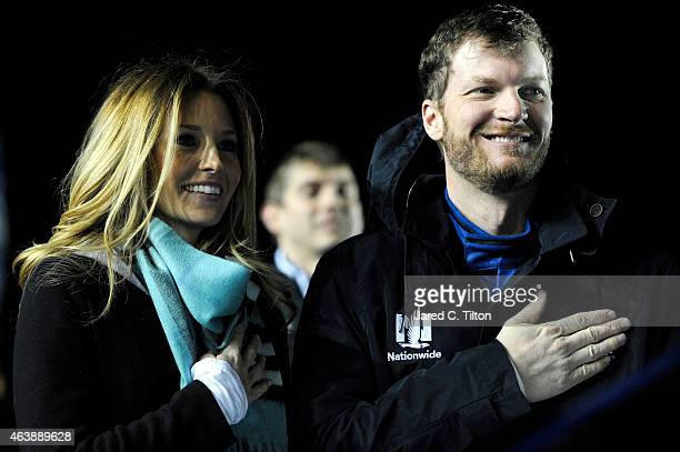 Dale Earnhardt Jr driver of the Nationwide Chevrolet right and girlfriend Amy Reimann participate in prerace ceremonies for the NASCAR Sprint Cup...