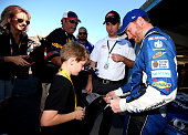 Dale Earnhardt Jr driver of the Nationwide Chevrolet signs autographs in the garage area during practice for the NASCAR Sprint Cup Series Quicken...
