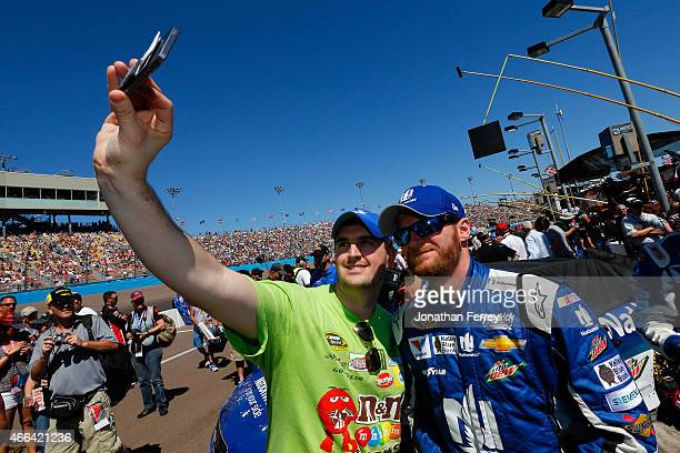 Dale Earnhardt Jr driver of the NATIONWIDE Chevrolet takes a picture with a fan prior to the NASCAR Sprint Cup Series CampingWorldcom 500 at Phoenix...