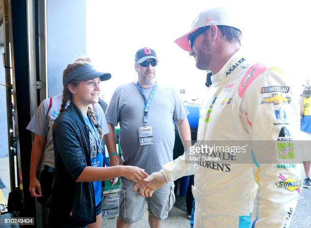 Dale Earnhardt Jr driver of the Nationwide Children's Hospital Chevrolet meets with Nationwide Children's Hospital patient Melanie Wheeler during...