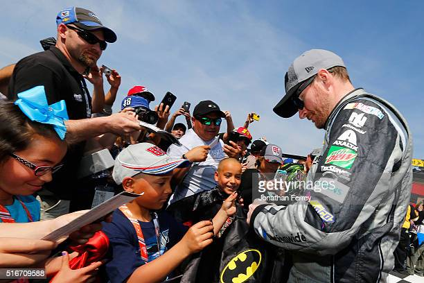 Dale Earnhardt Jr driver of the Nationwide Insurance / Batman Chevrolet signs autographs for fans before the NASCAR Sprint Cup Series Auto Club 400...