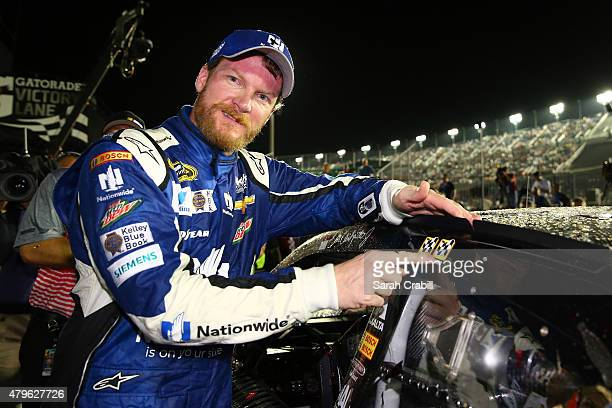 Dale Earnhardt Jr driver of the Nationwide Stars and Stripes Chevrolet affixes the winner's decal to his car in Victory Lane after winning the NASCAR...