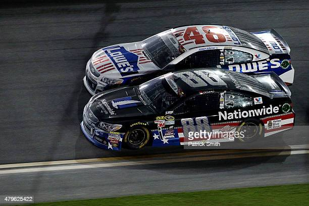 Dale Earnhardt Jr driver of the Nationwide Stars and Stripes Chevrolet races Jimmie Johnson driver of the Lowe's Patriotic Chevrolet during the...