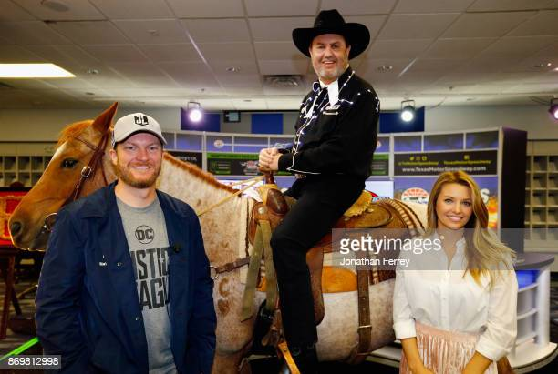 Dale Earnhardt Jr driver of the Nationwide/Justice League Chevrolet and his wife Amy Earnhardt pose with Texas Motor Speedway president Eddie Gossage...