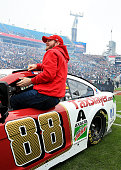 Dale Earnhardt Jr driver of the TaxSlayercom Chevrolet gets out of his race car on the field before the TaxSlayer Bowl game between the Georgia...