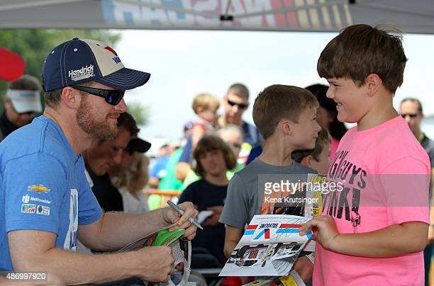 Dale Earnhardt Jr driver of the Valvoline Chevrolet left signs his autograph for young fans at an autgraph session prior to qualifying for the NASCAR...