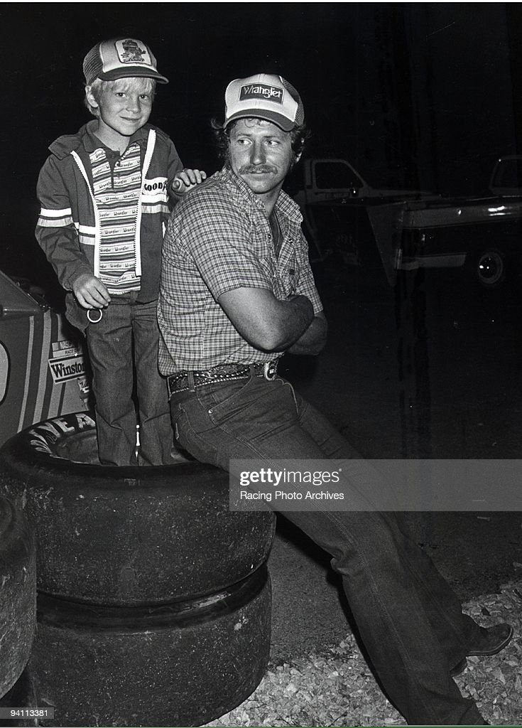 Dale Earnhardt Jr. gives the camera a smile while his father is distracted.