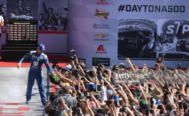 Dale Earnhardt Jr hands off a bottle of soda to fans during driver introductions at the Daytona 500 on Sunday Feb 26 2017 at Daytona International...