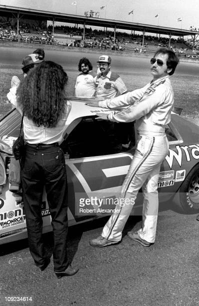 Dale Earnhardt Sr and his wife Teresa Earnhardt stand beside the Wrangler Ford Thunderbird prior to the start of the 1982 Daytona 500 at the Daytona...