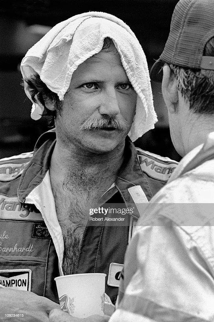 Dale Earnhardt Sr cools down and talks with Bobby Allison in the Daytona International Speedway garage after completing the 1985 Firecracker 400 on...