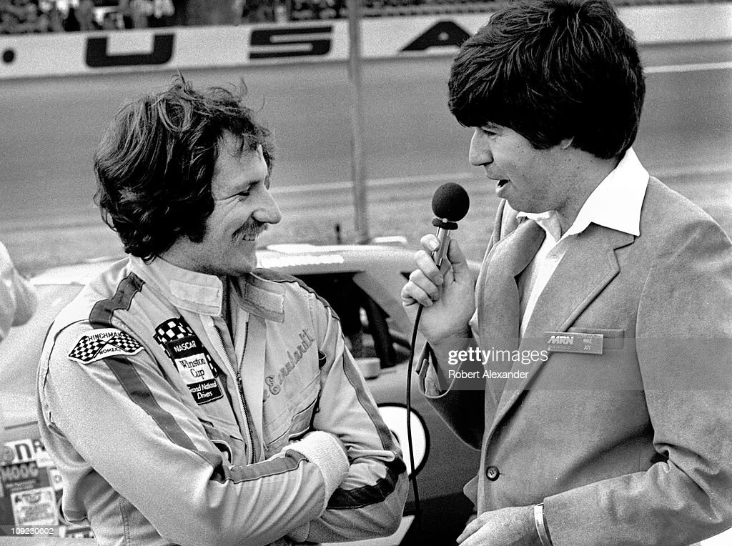 Dale Earnhardt Sr driver of the Wrangler Ford Thunderbird is interviewed by Motor Racing Network broadcaster Mike Joy prior to the start of the 1982...