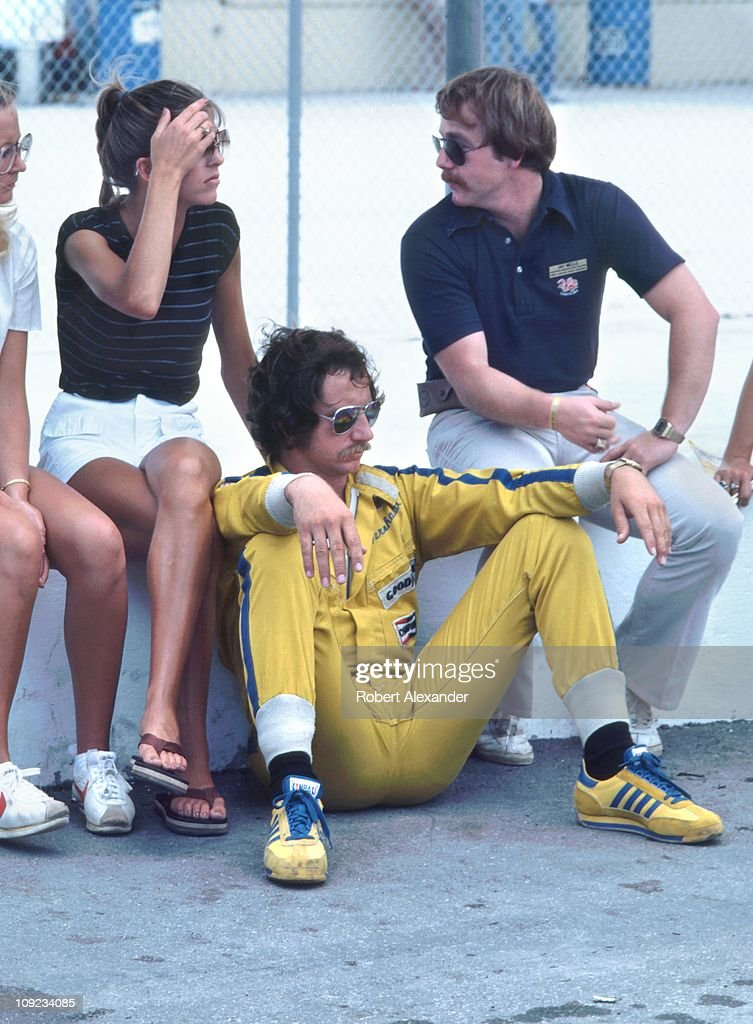 Dale Earnhardt Sr driver of the Wrangler Ford Thunderbird relaxes on pit road with his wife Teresa and others during qualifying for the 1982...