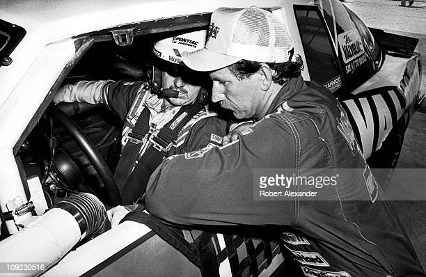 Dale Earnhardt Sr right talks with fellow driver and close friend Neil Bonnett in the garage at the Daytona International Speedway during practice...