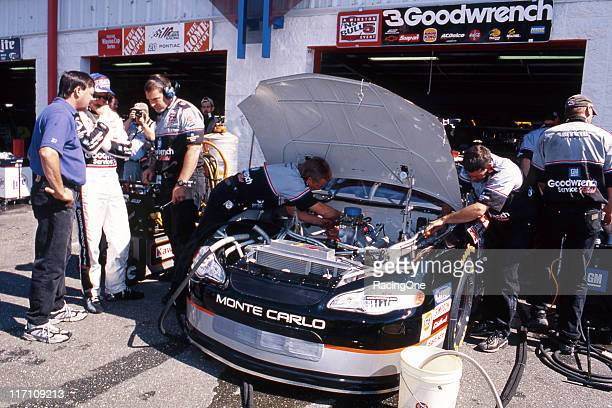 Dale Earnhardt watches as his Richard Childress Racing crew changes an engine in the garage area at a NASCAR Cup race