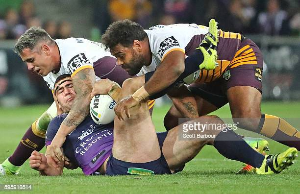 Dale Finucane of the Storm is tackled by Sam Thaiday and Corey Parker of the Broncos during the round 25 NRL match between the Melbourne Storm and...
