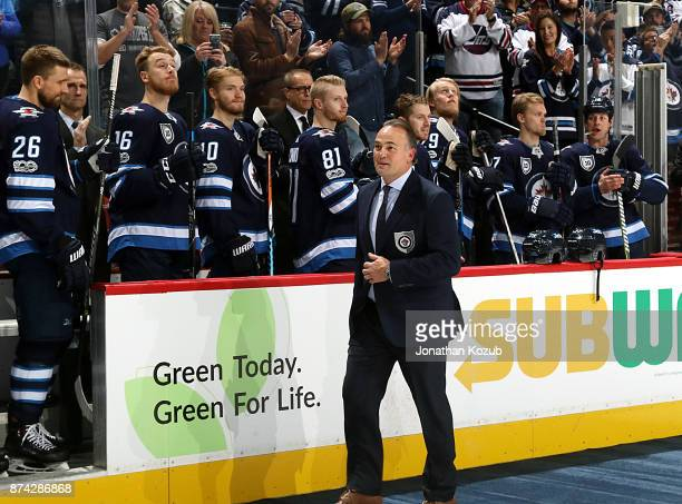 Dale Hawerchuk heads to centre ice for a ceremonial puck drop as he gets inducted into the Winnipeg Jets Hall of Fame prior to NHL action between the...