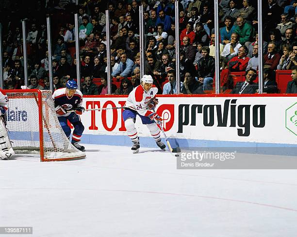 Dale Hawerchuk of the Winnipeg Jets hooks Chris Chelios of the Montreal Canadiens in 1981 at the Montreal Forum in Montreal Quebec Canada