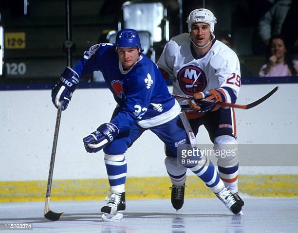 Dale Hunter of the Quebec Nordiques skates on the ice as Ken Leiter of the New York Islanders follows during their game circa 1987 at the Nassau...