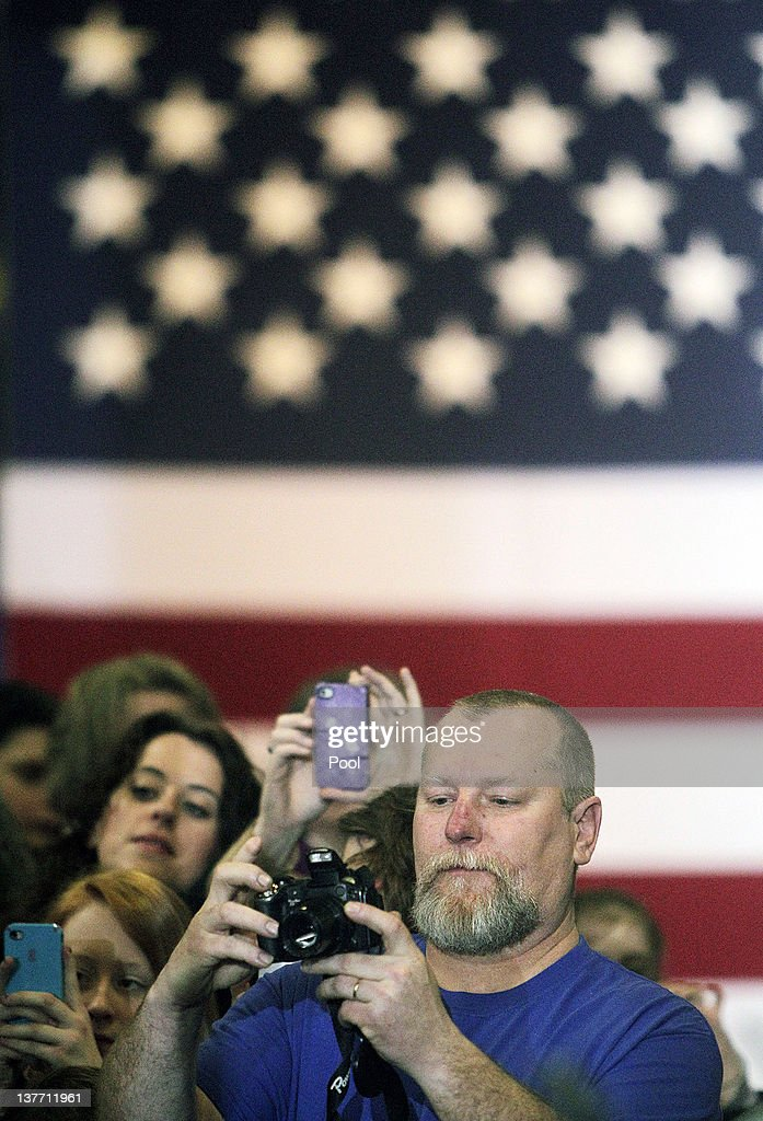 Dale Muldoon takes a photograph as U.S. President Barack Obama speaks to invited guests at Conveyor Engineering & Manufacturing January 25, 2012 in Cedar Rapids, Iowa. Obama, who is on a three-day tour, spoke about manufacturing and the economy during the speech.