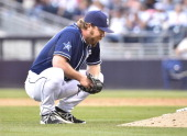 Dale Thayer of the San Diego Padres stands behind the mound after giving up a double during the tenth inning of a baseball game against the San...