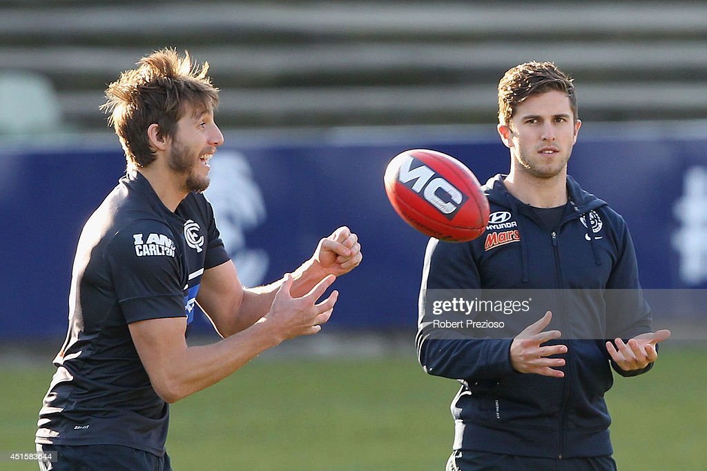 Dale Thomas handballs as Marc Murphy looks on during a Carlton Blues AFL training session at Visy Park on July 2, 2014 in Melbourne, Australia.