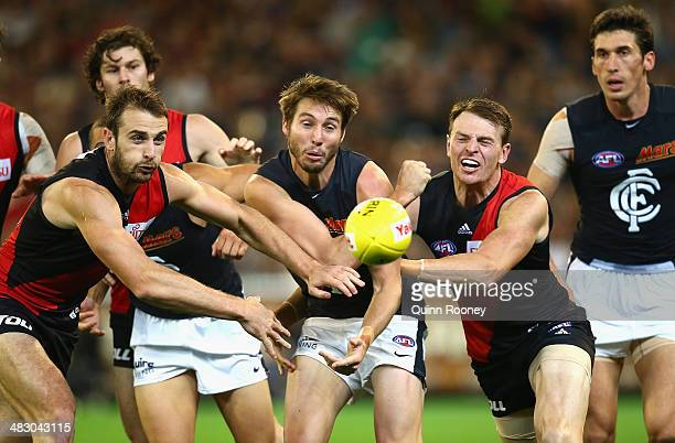 Dale Thomas of the Blues handballs whilst being tackled by Jobe Watson and Brendon Goddard of the Bombers during the round three AFL match between...