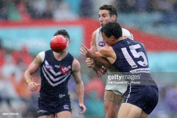 Dale Thomas of the Blues handpasses the ball under pressure from Ethan Hughes of the Dockers during the round nine AFL match between the Fremantle...
