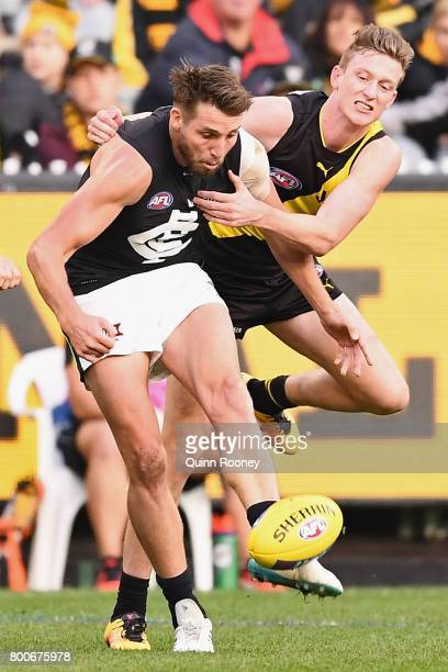 Dale Thomas of the Blues kicks whilst being tackled by Connor Menadue of the Tigers during the round 14 AFL match between the Richmond Tigers and the...