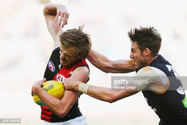 Dale Thomas of the Blues tackles Martin Gleeson of the Bombers during the round six AFL match between the Carlton Blues and the Essendon Bombers at...