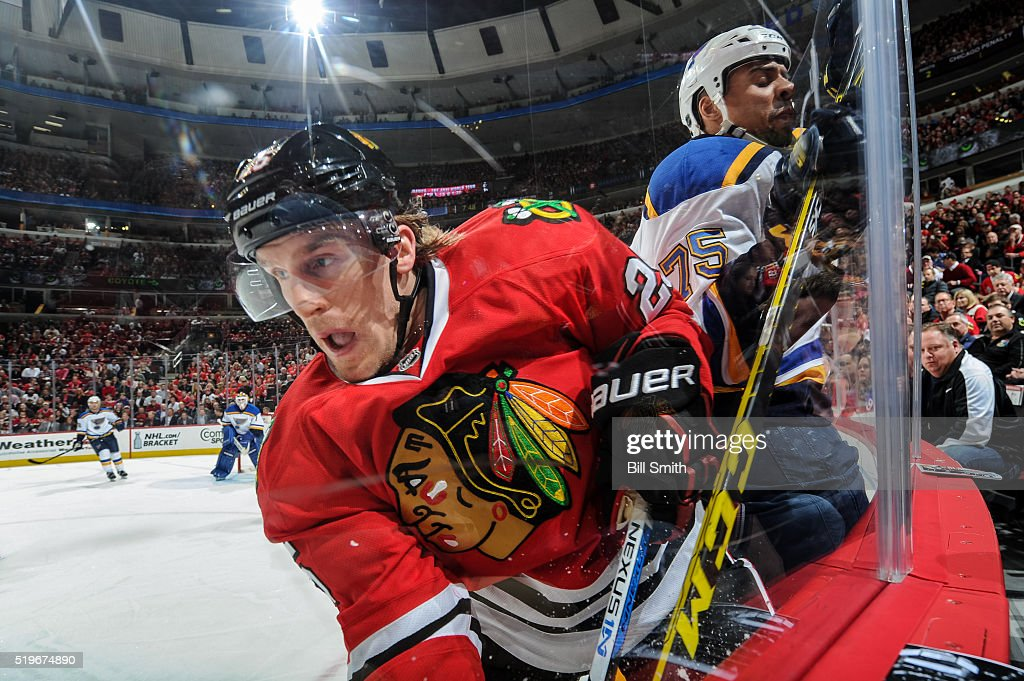 Dale Weise of the Chicago Blackhawks and Ryan Reaves of the St Louis Blues get physical by the boards in the first period of the NHL game at the...
